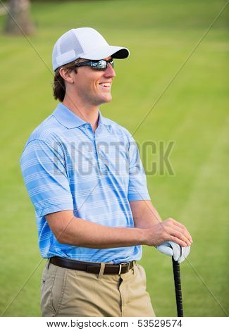 Athletic young man playing golf, Portrait of Golfer on Course
