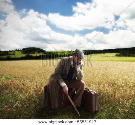 Emigrant In The Countryside Sitting On Cardboard Suitcases