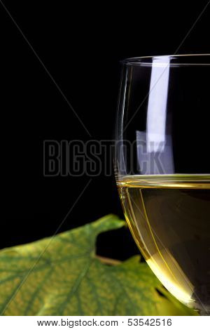 Closeup Of White Wine Glass In Front Of Vine Leaf