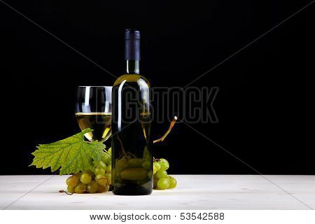 White Wine Bottle In Front Of White Grapes And Wine Glass