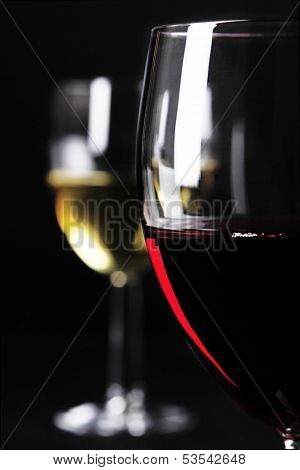 Closeup Of Red Wine Glass On Focus And Blurred White Wine Glass On Background