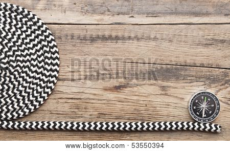 marine roll ropes and compass on wooden background