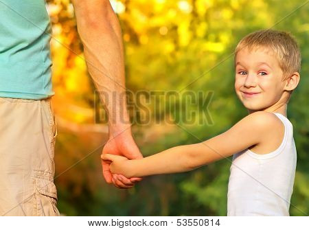 Happy Family Father Man And Son Boy Child Holding Hand In Hand Outdoor With Summer Nature On Backgro