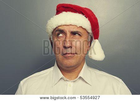 portrait of thoughtful santa man over dark background