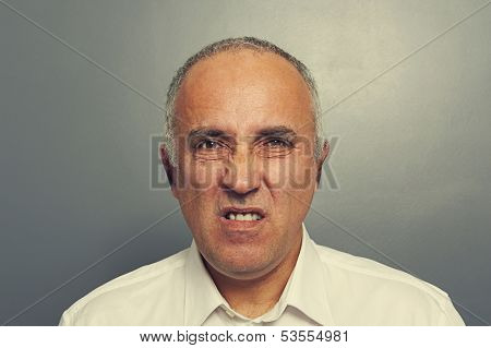 discontented senior man over dark background
