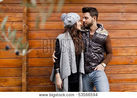 Young cheerful couple in a cabin in romantic scape in winter