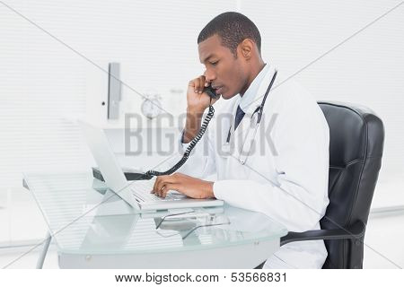 Side view of a concentrated male doctor using phone and laptop at medical office
