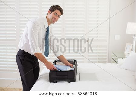 Side view portrait of a smiling businessman unpacking luggage at a hotel bedroom