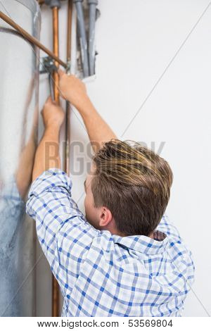 Rear view of a young technician servicing an hot water heater' pipes