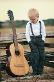 image of suspenders  - cute little boy with guitar on location - JPG