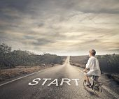 picture of cloudy  - little child pedaling a bicycle on a deserted road - JPG