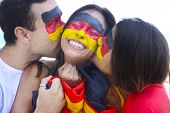 Happy group of three german soccer fans commemorating victory kissing each other.