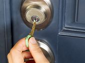 stock photo of insert  - Photo of female hand putting house key into front door lock of house - JPG