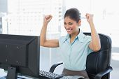 picture of clenched fist  - Elegant and happy businesswoman clenching fists while looking at computer in a bright office - JPG