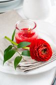 picture of buttercup  - Festive dining table setting with red buttercup flowers candles napkins and shiny new cutlery in white - JPG