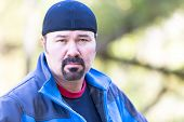 stock photo of goatee  - Man with a goatee looking determined attitude on a green sunny background - JPG