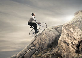 stock photo of pedal  - young businessman pedaling a bicycle on the rocks - JPG