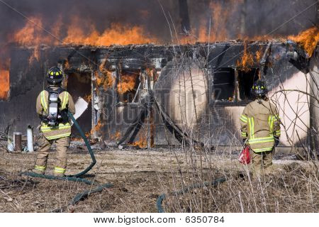 Firefighters Standing In Front Of A Burning House