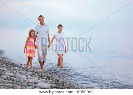 Familia feliz con la niña caminar en la playa de noche, enfoque en la madre