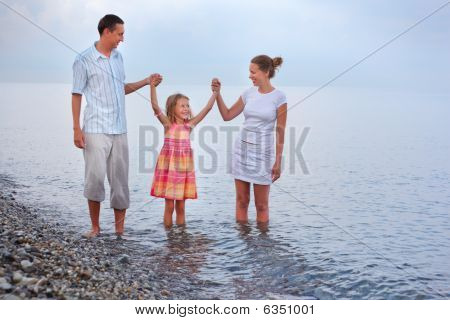 Happy Family With Little Girl Walk On Beach In Evening, Having Joined Hands