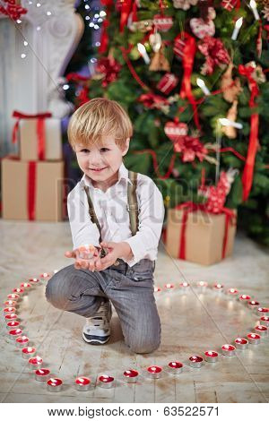 Little boy stands on floor on one knee among burning tealights and keeps one on his palm under Christmas tree