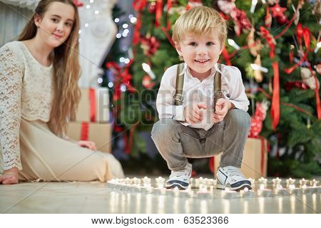 Little boy sits squatted among burning tealights that stand on floor in shape of heart under Christmas tree, teenage girl sits on floor a little further not in focus