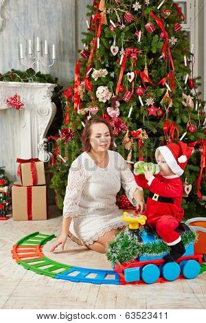 Mother sits on floor under decorated Christmas tree and look at little girl dressed in Santa suit which sits on toy plastic steam engine and drink from bottle