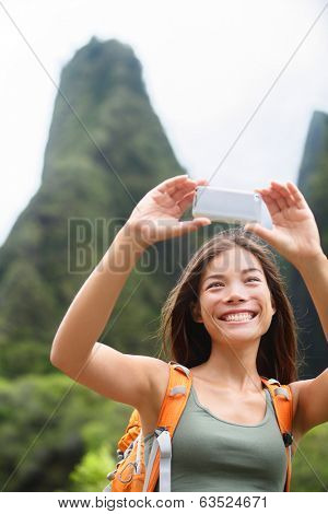 Woman hiker taking selfie photo using smartphone while hiking on Hawaii enjoying outdoor activity. Woman hiker taking photo with smart phone camera. Iao Valley State Park, Wailuku, Maui, USA.