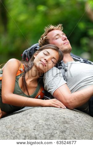 Hiking couple lovers relaxing sleeping in nature. Tried hikers resting lying down outdoors taking a break from hike. Young Asian woman and Caucasian man.