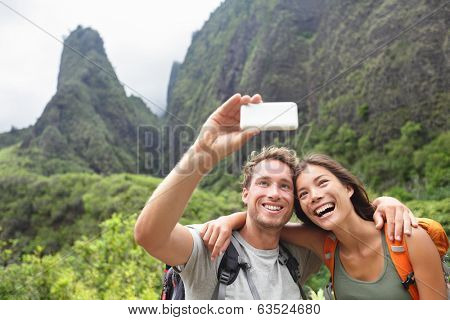 Couple taking selfie photo with smart phone hiking on Hawaii. Woman and man hiker taking photo with smart phone camera. Healthy lifestyle from Iao Valley State Park, Wailuku, Maui, Hawaii, USA.