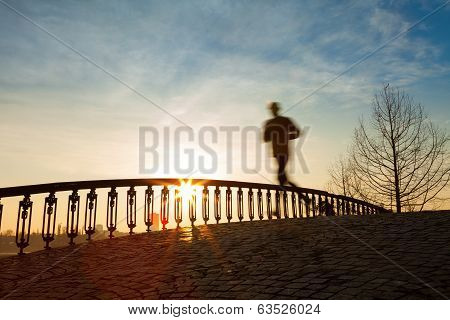 Jogger Running In Sunrise Over Bridge
