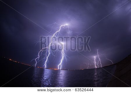 Thunderstorm And Lightnings In Night Over A Lake With Reflaction