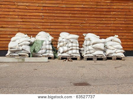 Sandbags In Five Piles With Wooden Wall In Background