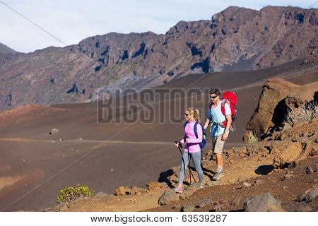 Hikers enjoying walk on amazing mountain trail. Backpacking in Haleakala volcano, incredible view. Couple trekking.