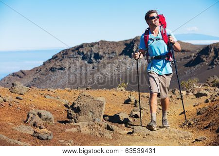 Hiker enjoying walk on amazing mountain trail. Backpacking in Haleakala volcano, incredible view. Trekking.