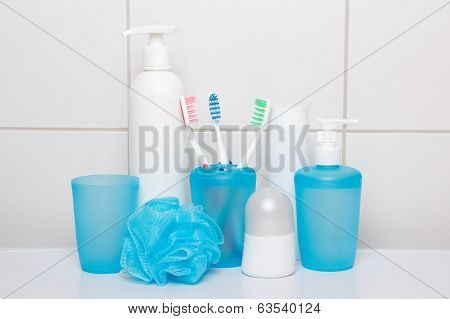 Set Of Blue Hygiene Supplies Over Tiled Wall