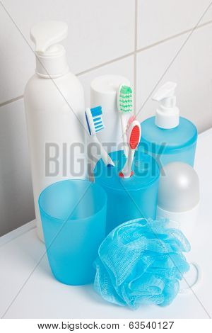 Set Of Blue Hygiene Supplies Over Tiled Wall In Bathroom