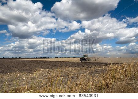 Tractor Plowing With Summer Clouds