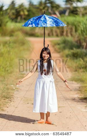 Beautiful young Thai girl balancing an open blue umbrella on her head as she stands on a rural path in the summer sunshine with a lovely smile and her arms outspread