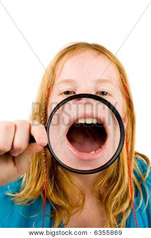 Little Girl Is Showing Her Mouth Through A Magnifying-glass