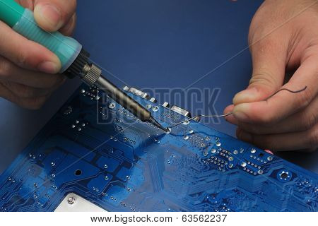 Closeup Of A Technician's Hands Soldering A Computer Mainboard