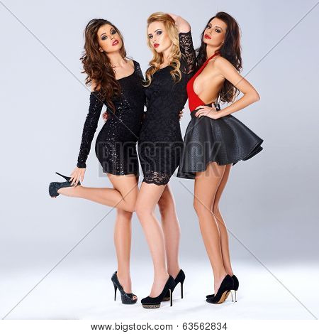 Three sexy elegant beautiful young women in black evening wear and stilettos posing close together looking seductively at the camera, full length studio portrait
