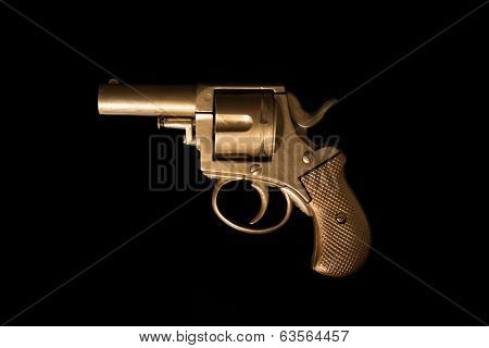 Old hand gun revolver with an aged golden patina displayed sideways on a dark background with copyspace