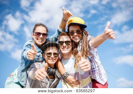 summer holidays and teenage concept - group of smiling teenagers in sunglasses hanging outside and showing thumbs up