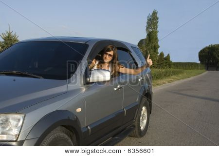 Happy Young Brunette Driving the Silver Car