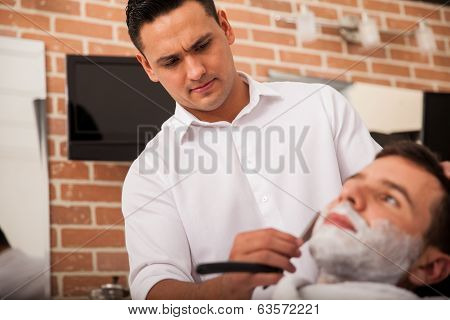 Hispanic Barber Shaving A Man