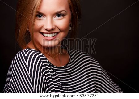 Portrait of smiling woman on black background. Close-up.