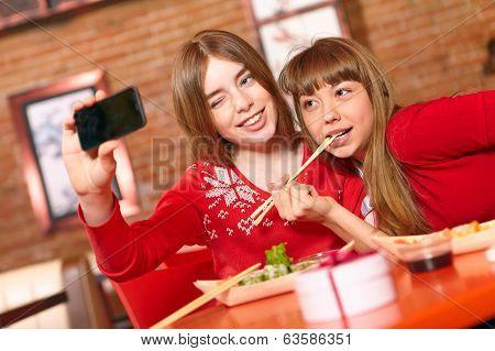 Beautiful Girls Eat Sushi Rolls At Sushi Bar.
