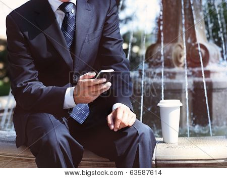 Businessman With A Mobile Phone And Coffee Near The Fountain