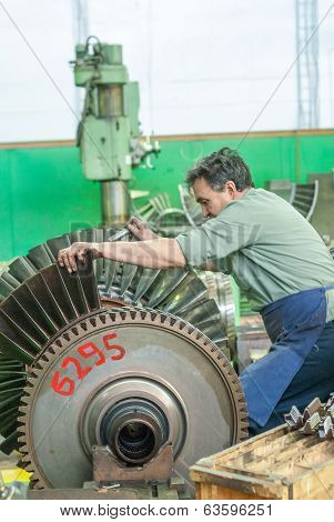 Mechanic assembles turbine for aviation engine